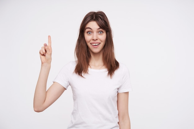 Open-eyed young pretty brunette female with casual hairstyle raising hand with having idea sign and rounding excitedly her eyes while looking , isolated over white wall