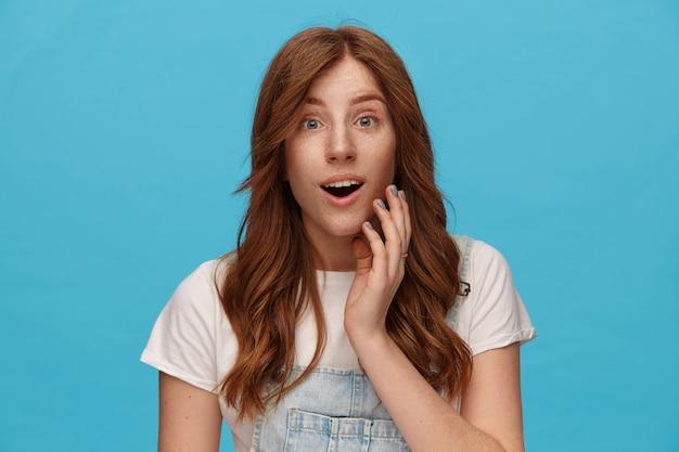 Signora giovane bella rossa dagli occhi aperti con trucco naturale guardando sorpreso la fotocamera con la bocca aperta e alzando la mano al viso, isolato su sfondo blu