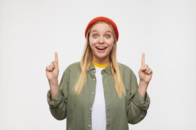 Giovane donna dalla testa bianca con gli occhi aperti vestita con cappello rosso, camicia verde oliva e maglietta bianca che si presenta con le dita indice e guarda sorpresa, isolata sul blu