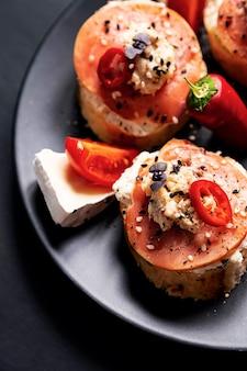 오픈 페이스 샌드위치 속을 채운 생선 크림 치즈 토마토 칠리 페퍼와 참깨
