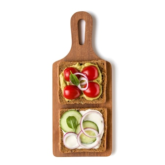 Open  faced vegetable sandwich canape or crostini on a wooden serving board