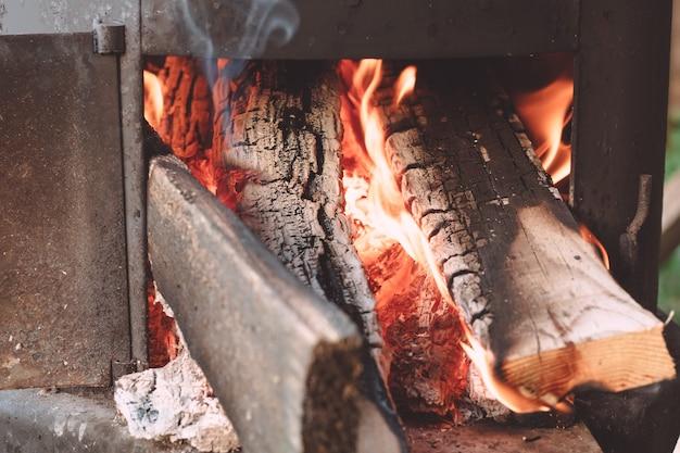 薪が燃えている庭の大釜の火室を開く