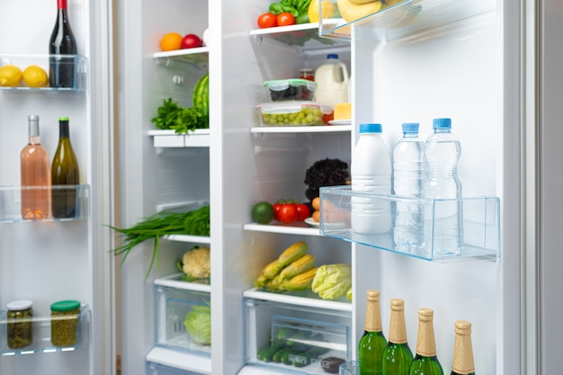 Open fridge full of fresh fruits, vegetables and drinks
