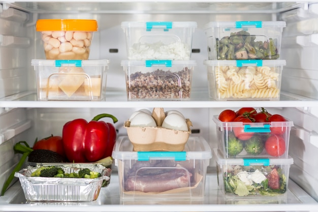 Open fridge with plastic food containers and vegetables