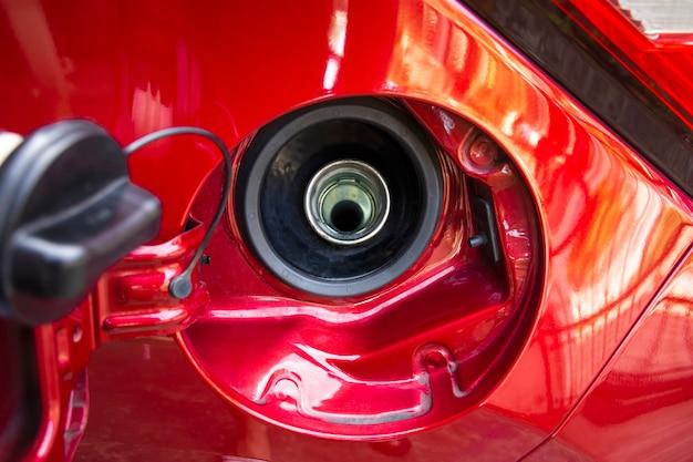 赤い車の開いた燃料タンクのキャップをクローズアップ