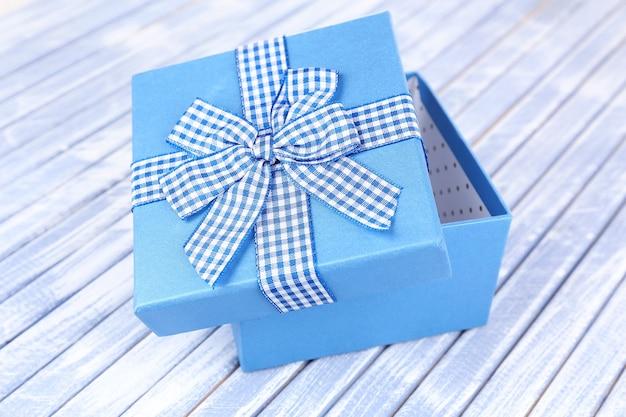 Открытая подарочная коробка на деревянном фоне