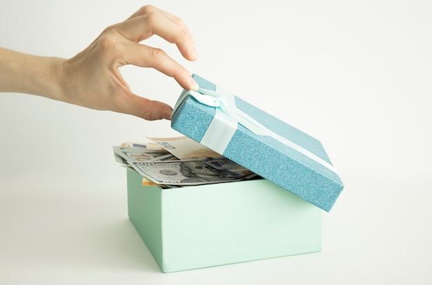 Откройте подарочную коробку с большой золотой монетой внутри на столе. концепция денежного подарка.