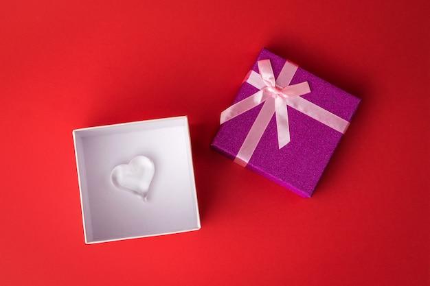 Открытая подарочная коробка со стеклянным сердцем на красном фоне. признание в любви.