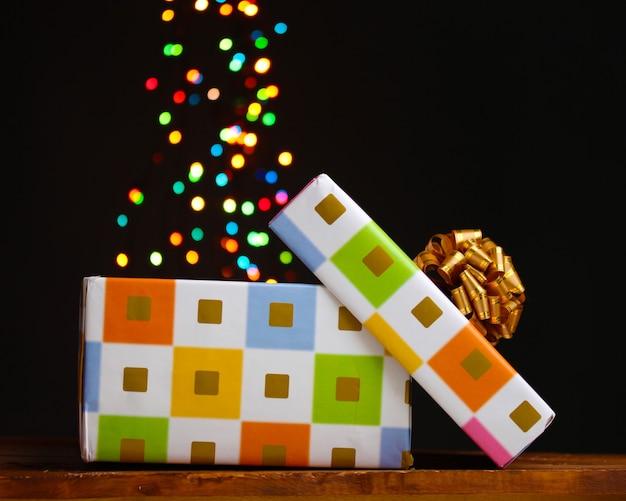 Открытая подарочная коробка с фоном боке на черном
