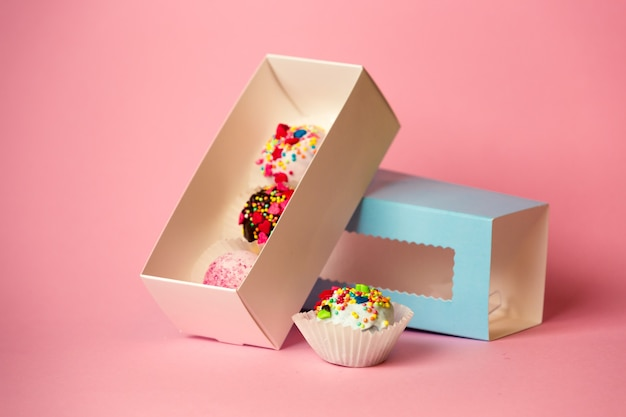 다채로운 케이크 볼과 스프링클이 있는 사탕이 있는 열린 선물 상자