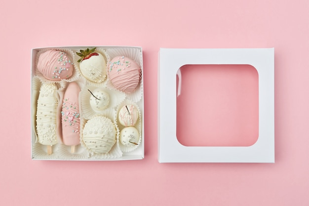 Открытая подарочная коробка с фруктами в белом и розовом шоколаде на розовом