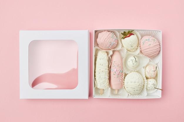 Открытая подарочная коробка с фруктами в белом и розовом шоколаде