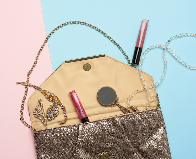 Open gold clutch and dropped bracelets with shiny stones