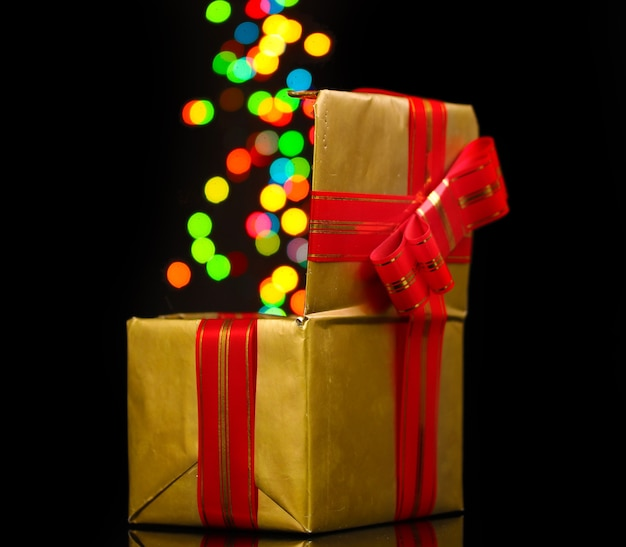 Open golden gift box with blurred lights on black
