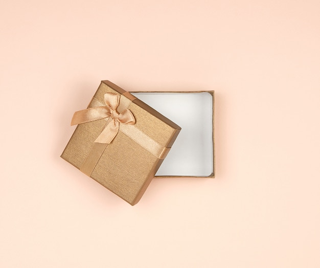 Open golden gift box with a bow on beige