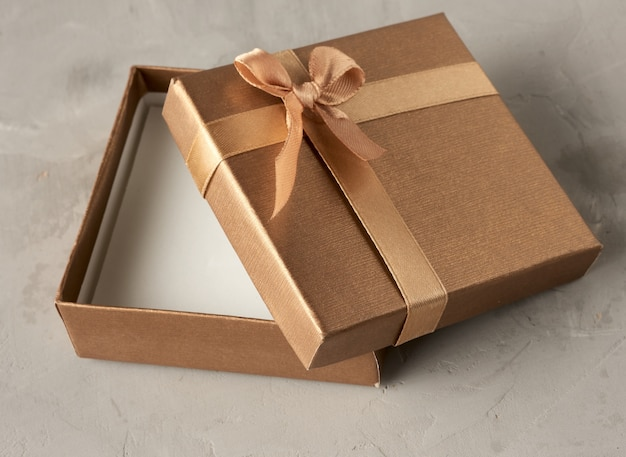 Open golden square gift box on gray background