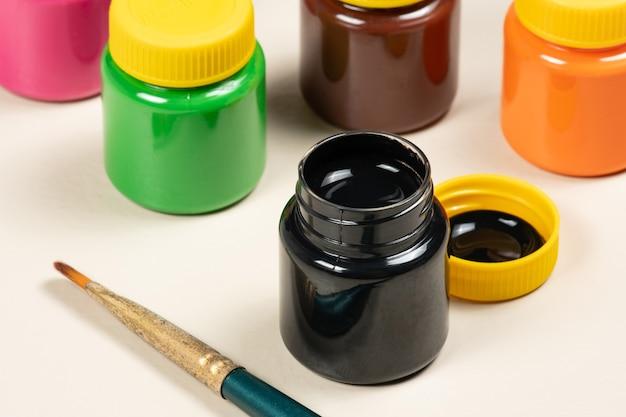Раскройте стакан с краской гуашью на фоне других трубок