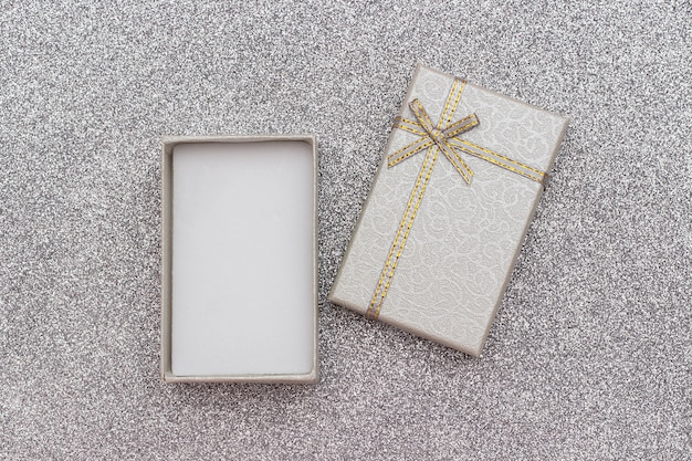 Open gray gift box with bow on silver shiny background.
