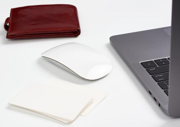 オープングレーのラップトップは、ワイヤレスマウス、フリーランサーの職場の横にある白いテーブルの上に立っています。