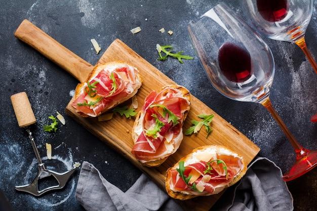 오픈 햄 샌드위치, arugula 및 단단한 치즈, 콘크리트 오래된 어두운 표면에 레드 와인 한 잔과 함께 나무 스탠드에 제공