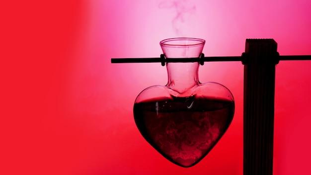 흐릿하고 분홍색 배경에 하트 모양의 빨간 사랑의 물약을 엽니다.