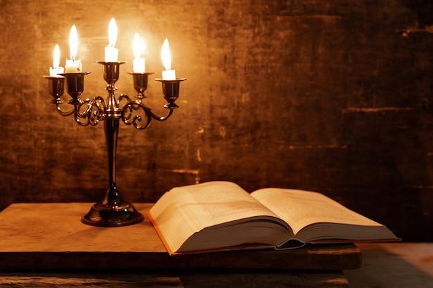 오래 된 오크 나무 테이블에 성경과 촛불을 엽니 다. 아름 다운 금 배경입니다. 종교 개념.