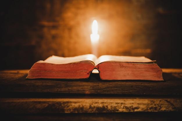 오래 된 오크 나무 테이블에 성경과 촛불을 엽니 다.