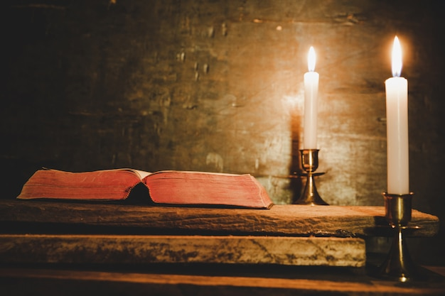 Open holy bible and candle on a old oak wooden table.