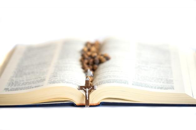 十字架の光の中で聖書を開きます。信仰、精神性、キリスト教の宗教概念。