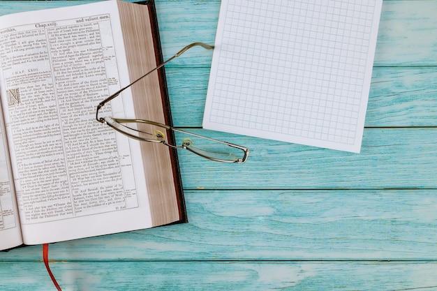 Открытая библия, лежа на деревянном столе в чтении в блокноте