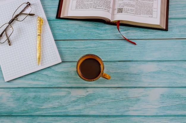 Открытая библия, лежа на деревянном столе в чтении с чашкой кофе