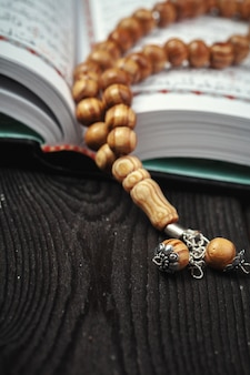 The open holy quran with tasbih beads
