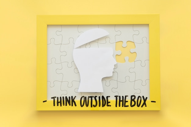 Open human brain and incomplete jigsaw puzzle frame with think outside the box message