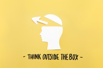Open human brain with arrow symbol near think outside the box message
