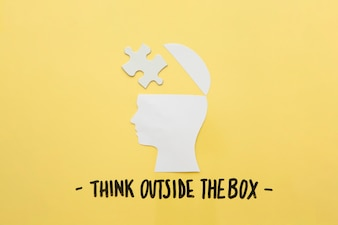 Open human brain with jigsaw piece near think outside the box message