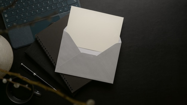 Open  invitation card with grey envelope above black schedule books with supplies and decoration