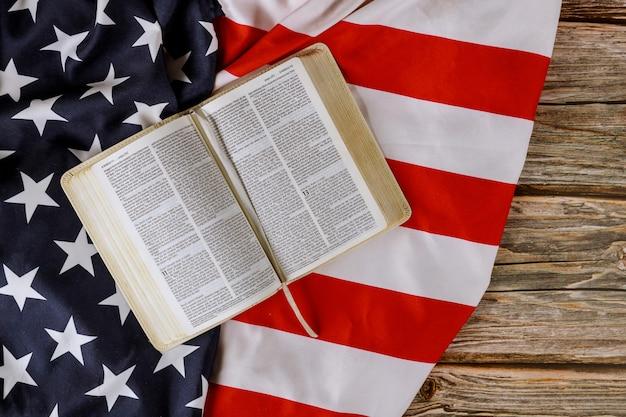 オープンは木製のテーブルでフリルアメリカの国旗をめぐってアメリカの祈りで聖書の本を読んでいます。