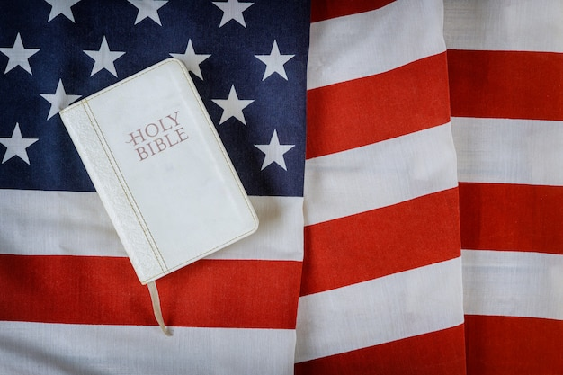 Открытый читает книгу библии с молитвой за америку над взъерошенным американским флагом на деревянном столе