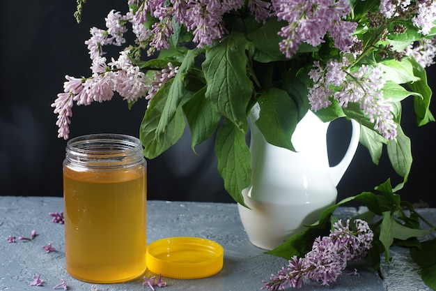 An open jar of linden honey stands on a table next to a bouquet of purple lilac in a white jug.