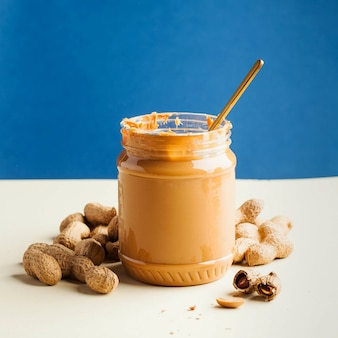 An open jar of peanut butter with a spoon and peanuts in the shell around on a colored wall. quick breakfast, food for vegetarians.