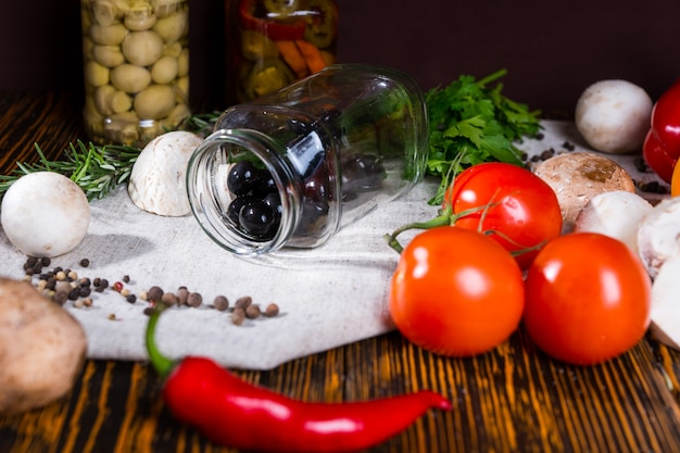 Open jar with black olives lies on a napkin near spices, tomatoes, mushrooms and other vegetables on wooden table