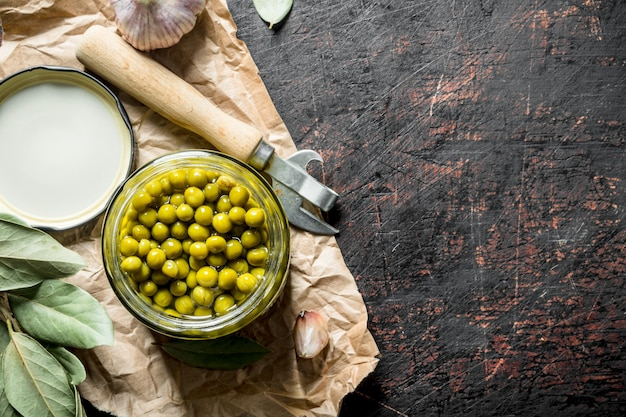 Open jar with canned green peas on paper on dark rustic table.