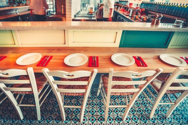 오픈 키친. 현대적이고 심플한 카페 인테리어는 목재 가구 - 동쪽 스타일의 모자이크 바닥, 바 테이블 카운터 및 흰색 의자를 제공합니다. 외부 식사 및 통신의 개념입니다. 컬러 필터