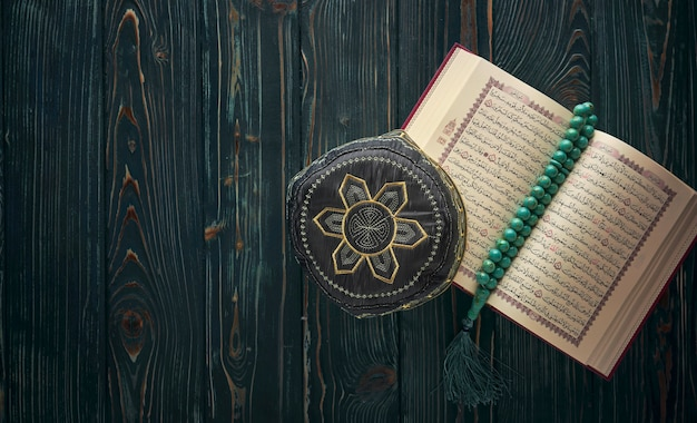 Open koran with rosary beads and muslim hat
