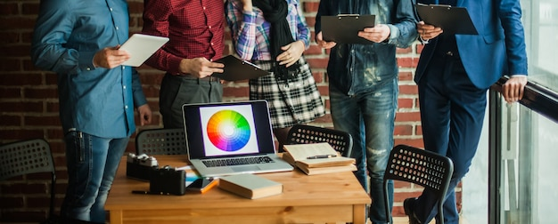 Открытый портативный компьютер с цветовой палитрой на рабочем месте дизайнера