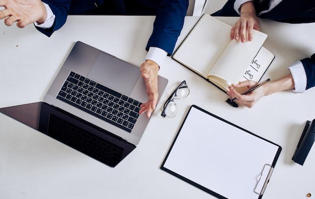 Открытый ноутбук документы бизнес финансы очки блокнот мужчина и женщина вид сверху. фото высокого качества