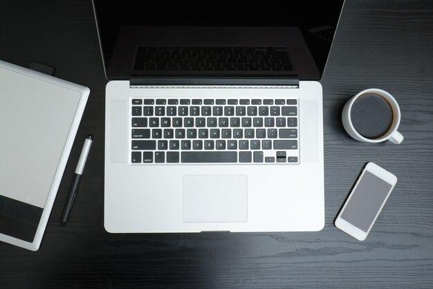 黒いテーブル、上面図でラップトップ、グラフィックタブレット、スマートフォン、コーヒーマグを開く