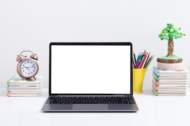 本の目覚まし時計のオンライン学習の概念で子供の職場でラップトップのモックアップを開きます