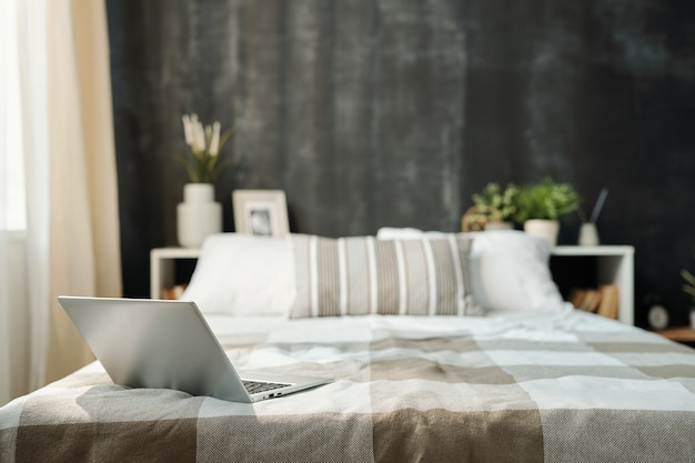 Open laptop on neatly made bed with linen checkered plaid and group of pillows