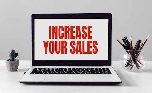 텍스트가있는 오래된 흰색 책상에 노트북을 열어 판매를 늘리십시오.